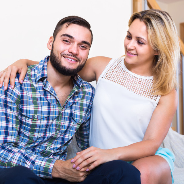 """""""Portrait of young couple sitting on couch"""" stock image"""