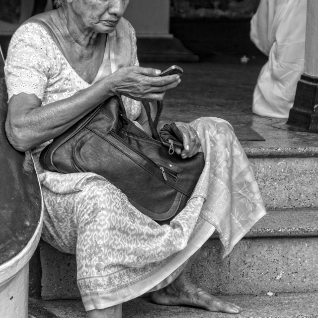 """Old woman sitting at the entrance to a temple"" stock image"