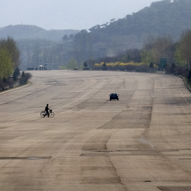 """""""North Korean man with a bicyle crossing an empty highway in North Korea,..."""" stock image"""
