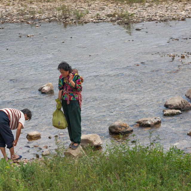 """North Korean women walking on stones to cross a river, North Hwanghae..."" stock image"