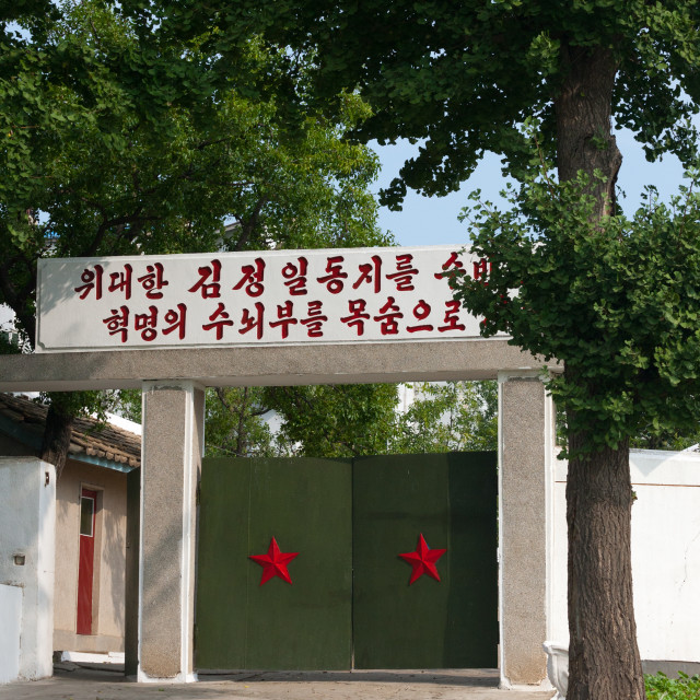 """""""Entrance gate with red stars and a propaganda slogan above, Kangwon Province,..."""" stock image"""