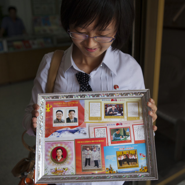 """North Korean woman showing Kim jong-un postage stamps, North Hwanghae..."" stock image"