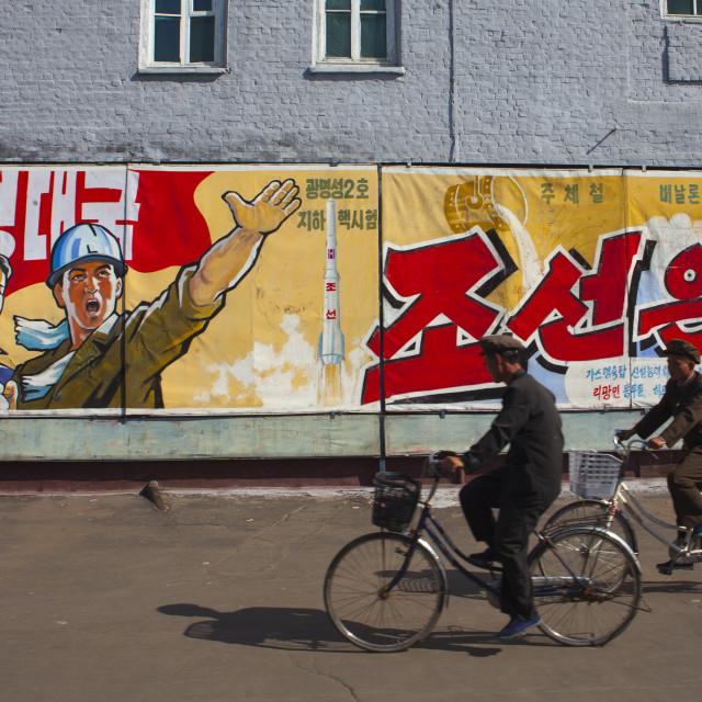 """North Korean men riding bicycles in front of propaganda billboards in Hungnam..."" stock image"