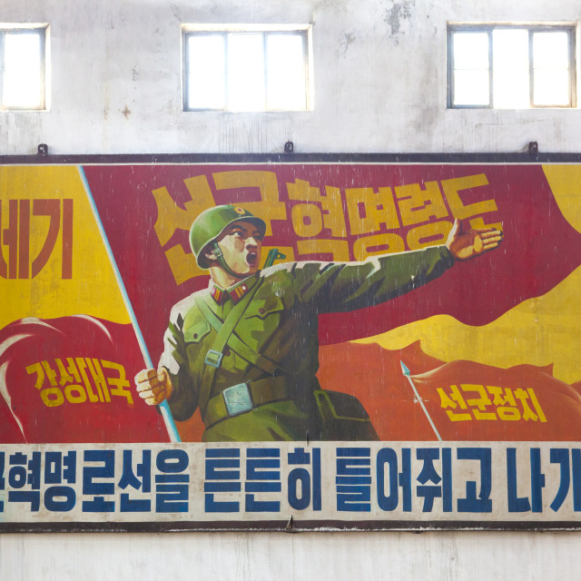 """Propaganda billboard with a soldier inside Hungnam nitrogen fertilizer plant,..."" stock image"