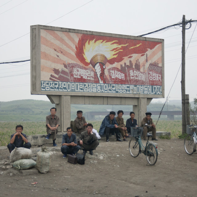 """North Korean workers having a rest below a juch tower flame billboard, South..."" stock image"