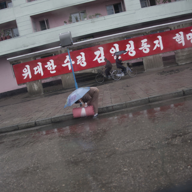 """North Korean woman bending over in the street, South Hamgyong Province,..."" stock image"