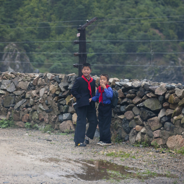 """""""Two North Korean boys standing next to a high fence on a road, North Hamgyong..."""" stock image"""