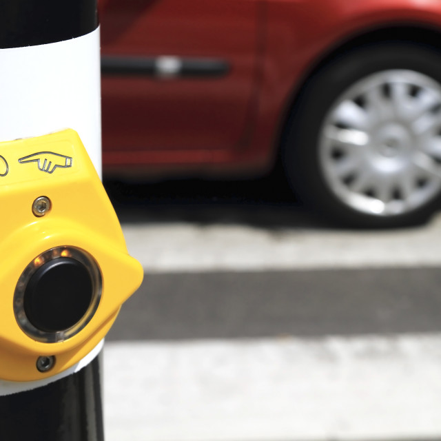 """Yellow crosswalk button red car"" stock image"