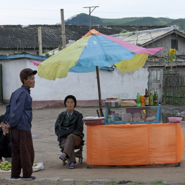 """Food and drinks street vendor sitting under umbrella, North Hamgyong..."" stock image"