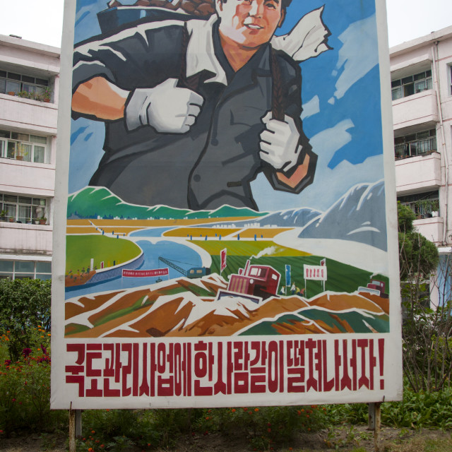 """Large propaganda billboard with a smiling worker, North Hwanghae Province,..."" stock image"