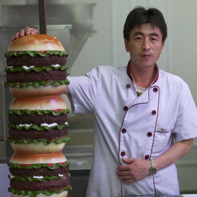 """North Korean cook with a giant hamburger in a fast food restaurant, Pyongan..."" stock image"