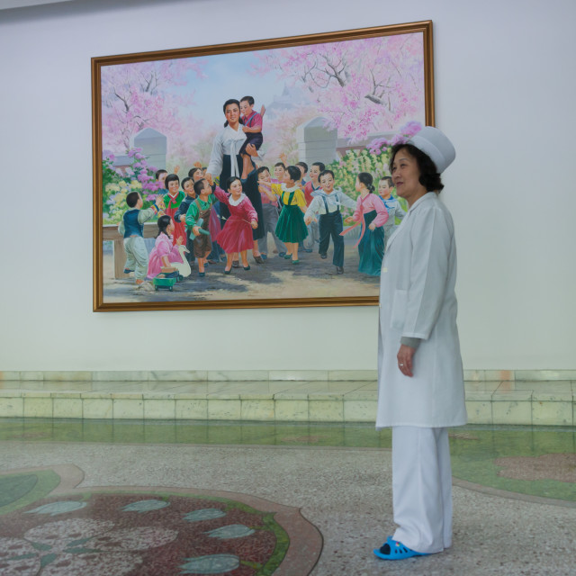 """North Korean school employee in front of a propaganda poster with Kim Jong..."" stock image"