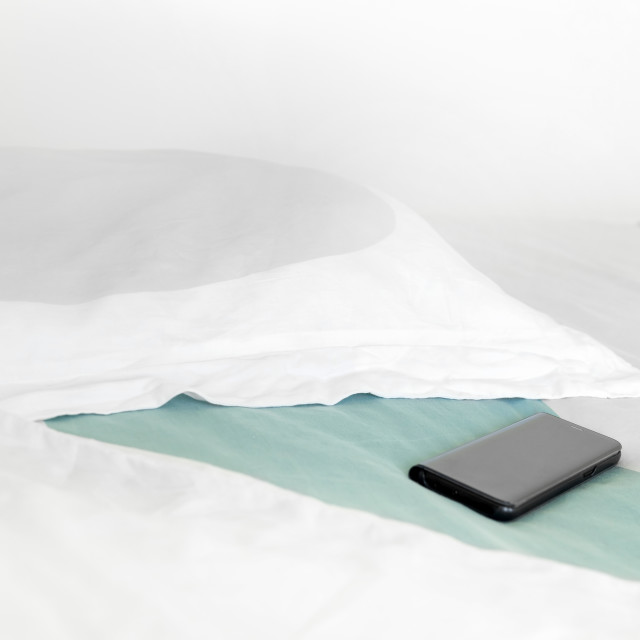 """Mobile phone on a bed"" stock image"