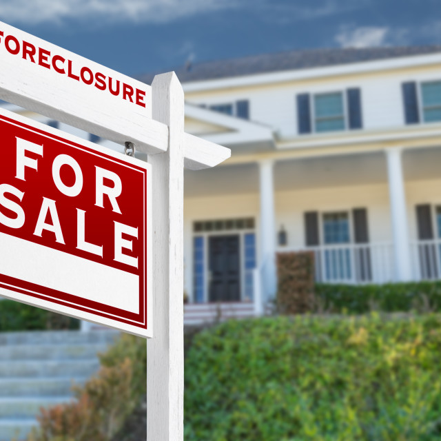 """Left Facing Foreclosure For Sale Real Estate Sign in Front of House."" stock image"