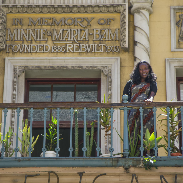 """""""African woman on balcony at Art and craft shop, Long Street, Cape Town"""" stock image"""