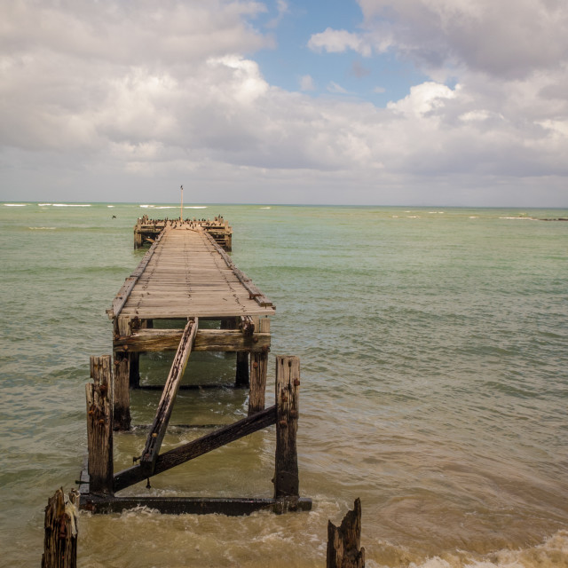 """Old wooden jetty. Broken and slowly falling into the sea."" stock image"