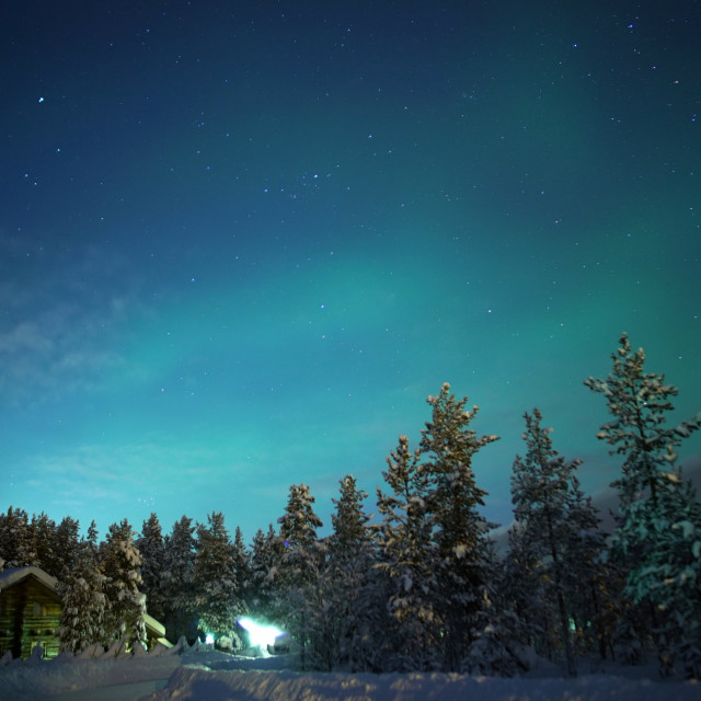 """A wooden cabin sits under the Northern Lights"" stock image"