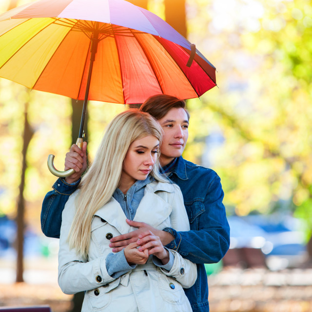 """Couple embracing under umbrella in sunlight day."" stock image"