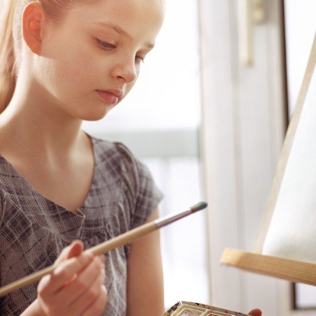 """""""Artist painting on easel in studio. Girl paints with brush."""" stock image"""