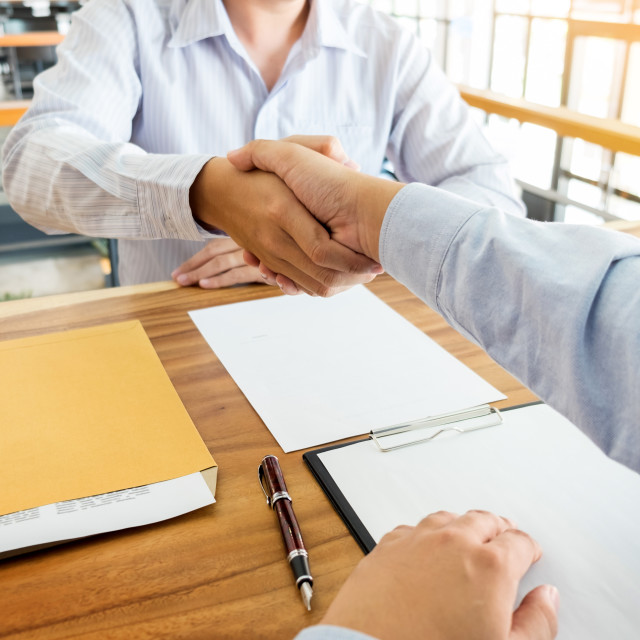 """Two confident business man shaking hands during a meeting in the"" stock image"