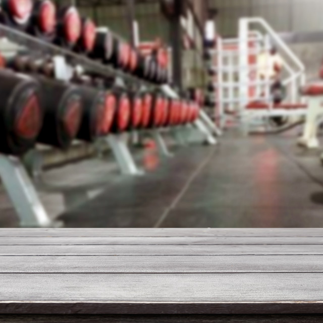 """Wooden table on blurred background of fitness gym interior of mo"" stock image"