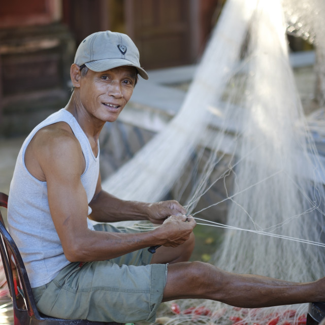 """Vietnamese fisherman mending a net"" stock image"