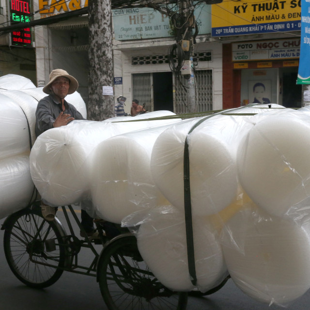 """""""Man pedals a trishaw, loaded with rolls on a road. Ho Chi Minh City. Vietnam."""" stock image"""