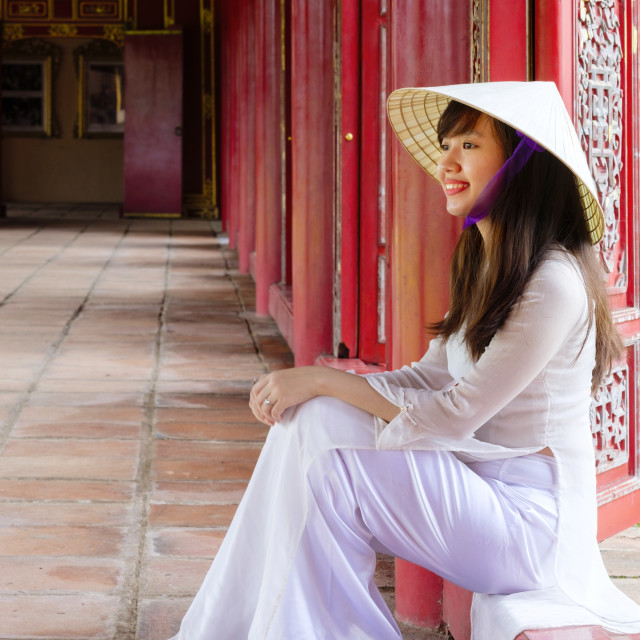 """Young Vietnamese woman in a traditional Ao Dai dress and Non La conical hat"" stock image"