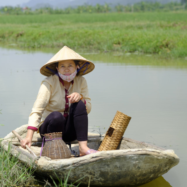 """Local village fisher woman wearing a Non La conical hat and sitting in a..."" stock image"