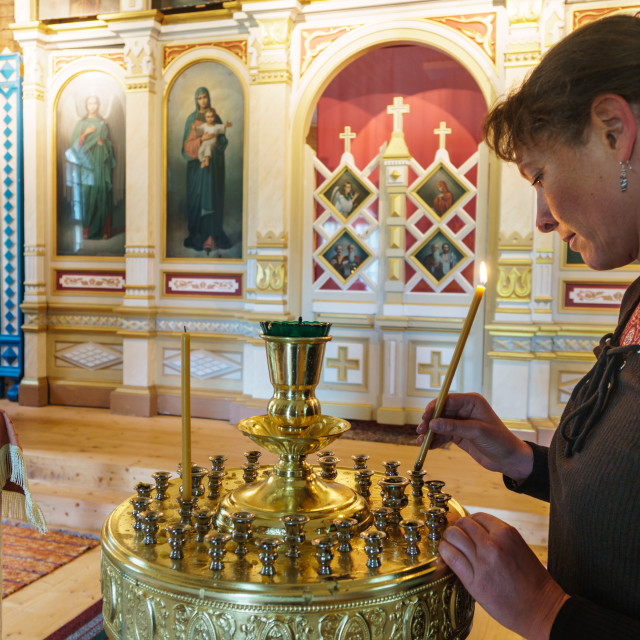 """""""Local woman cleaning the candle holder at Obinitsa Orthodox Church (built..."""" stock image"""