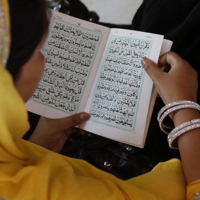 """Woman reading Kuranic scriptures in Nizamuddin dergah, Delhi, India."" stock image"