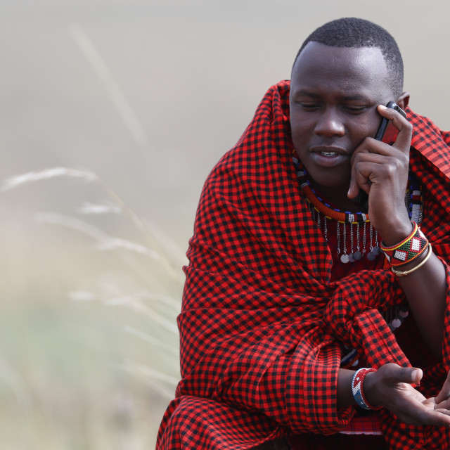 """A Masai man talking on a mobile phone in the african savanna. Masai Mara game..."" stock image"