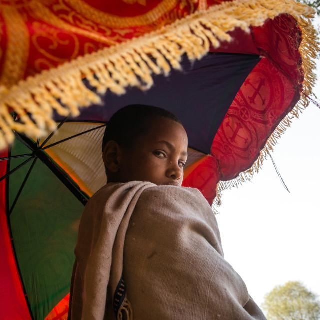 """""""Boy holding an umbrella during kidane mehret orthodox celebration, Amhara..."""" stock image"""