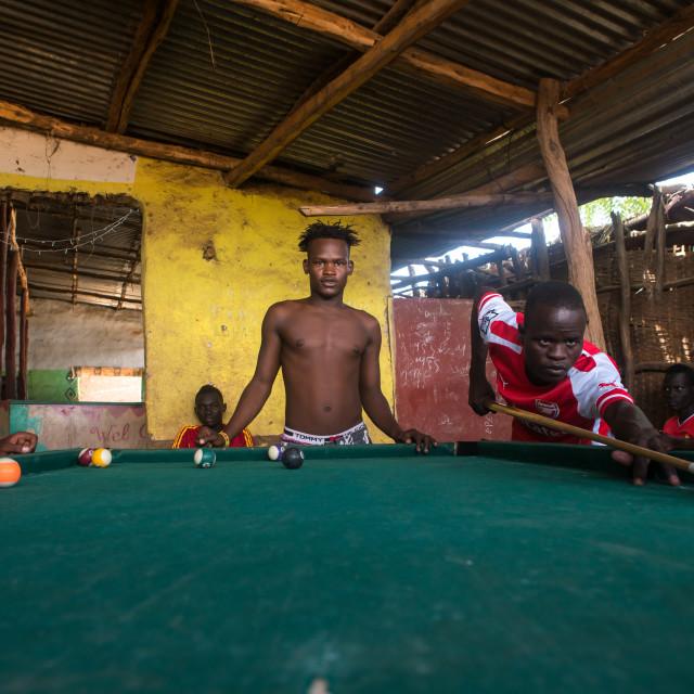 """Young men playing snooker pool, Omo valley, Kangate, Ethiopia"" stock image"