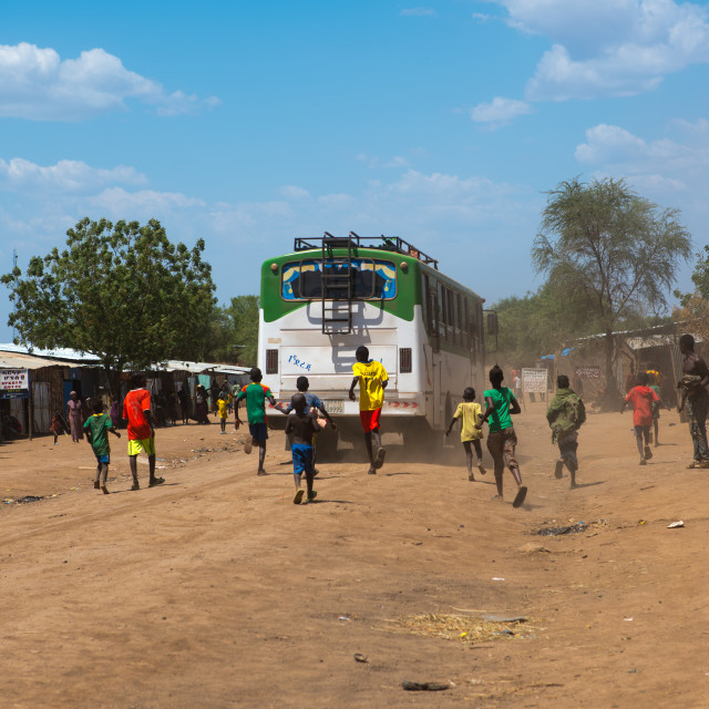 """""""Children running after a bus on a dusty road, Omo valley, Kangate, Ethiopia"""" stock image"""