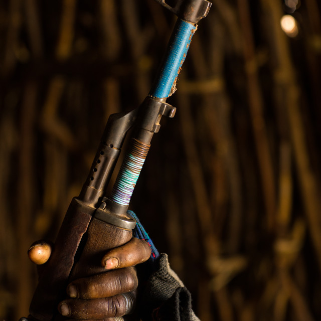 """""""Nyangatom tribe woman holding a kalashnikov in her hut, Omo Valley, Kangate,..."""" stock image"""