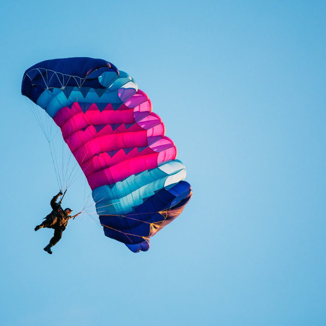 """""""Skydiver On Colorful Parachute In Blue Clear Sky"""" stock image"""