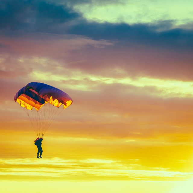 """""""Skydiver On Colorful Parachute In Sunny Sunset Sky. Active Hobbies."""" stock image"""