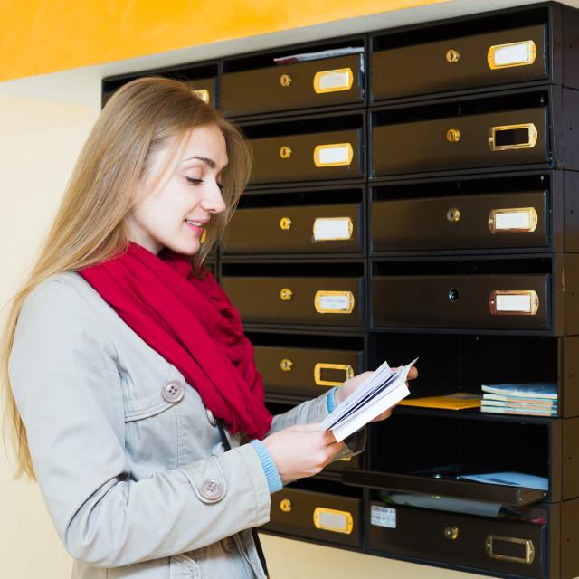 """Woman checking correspondence at lobby"" stock image"