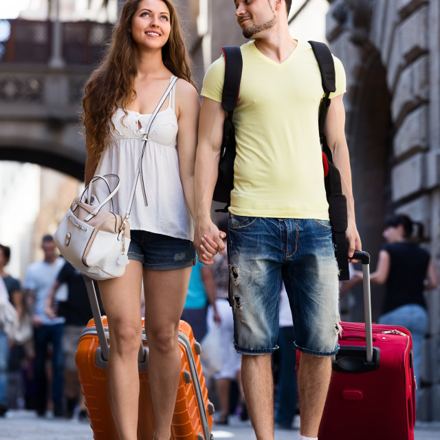 """Smiling young couple in shorts walking through city"" stock image"