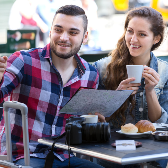 """Tourists drinking coffee and examining map"" stock image"