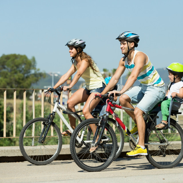 """Family of four cycling on street"" stock image"