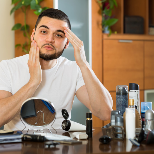 """man applying facial cream at home"" stock image"