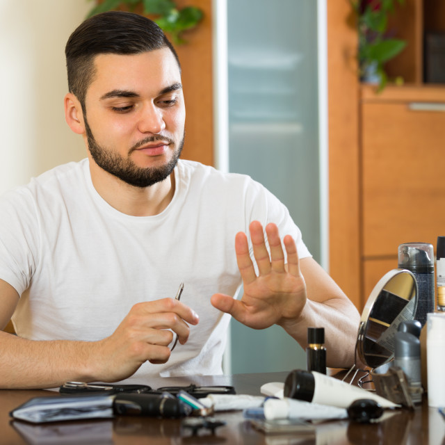 """Young guy cutting nails"" stock image"