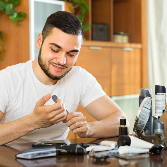 """Man doing manicure at home"" stock image"