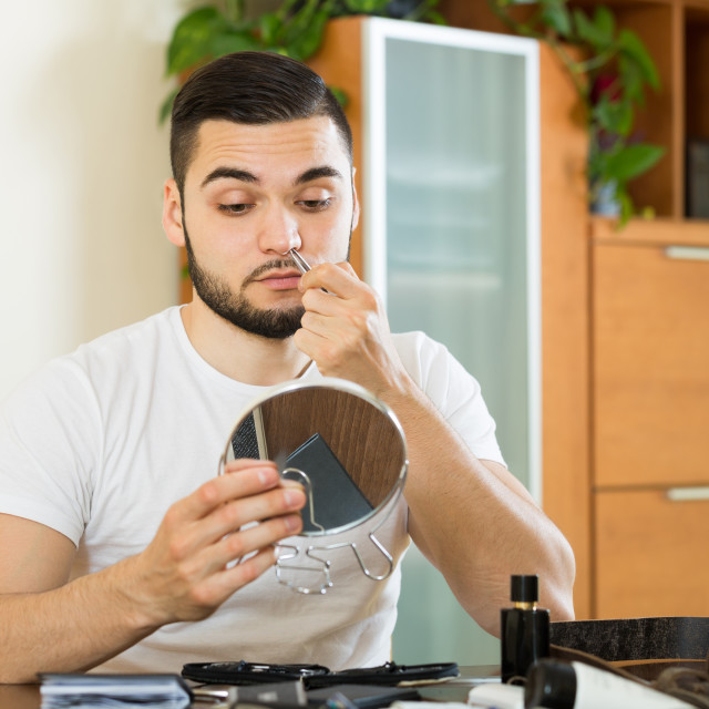 """Man plucking hair from his nose with pliers"" stock image"