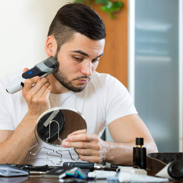 """Shaving face with electric razor"" stock image"