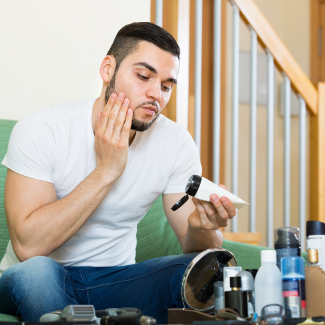 """Handsome man applying facial cream at home"" stock image"