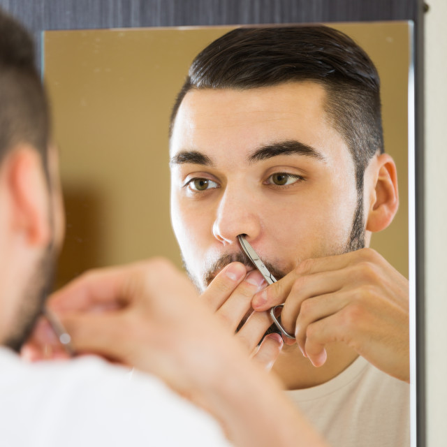 """Man looking at mirror and shaving face with razor"" stock image"