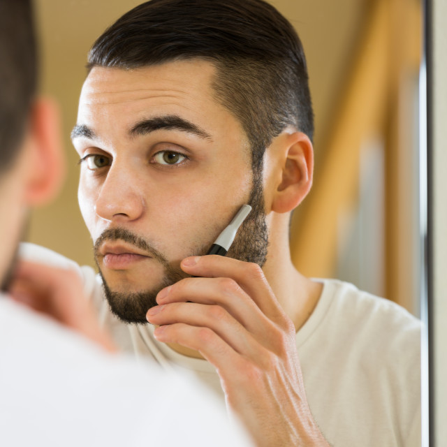 """Man looking at mirror and shaving beard with trimmer"" stock image"